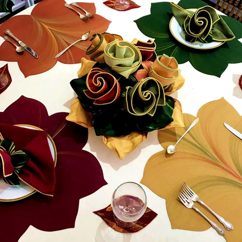Thanksgiving Collection Placemats Napkins and Rings as settings on a Tablecloth