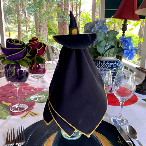 """This very good Witch Napkin Doll includes one easy-care black/silver napkin and hand-painted hat ring-to-coaster. Drop over a wine bottle for dramatic """"flying"""" height, as shown here."""
