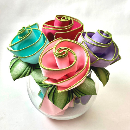 Four delicious springtime colors tipped with honeydew trim come together with leafy mint napkin rings. Shown here, light pink, hot pink, lilac and aqua.
