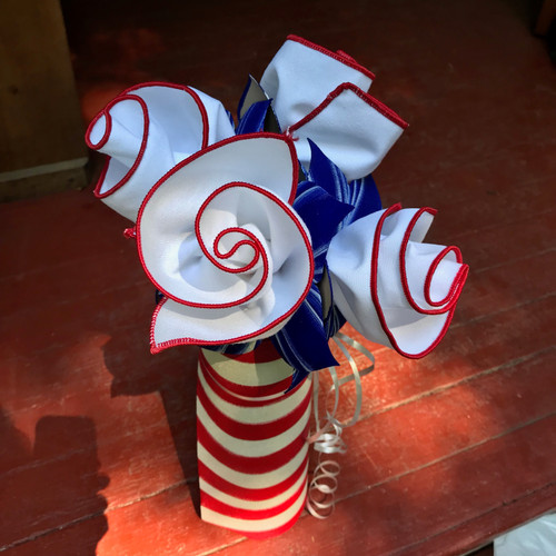 Four crisp white napkins with red trim are rolled up with four hand-painted blue and white napkins rings, tucked into a rolled up hand-painted red and white striped rectangular placemat/centerpiece. Bring on the Fireworks!