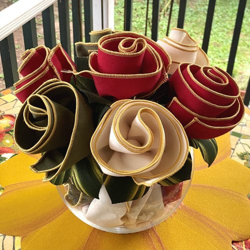 Botanical Napkin Bouquet includes 2 Red/Gold, 2 Ivory/gold and 2 Olive/gold Napkins, gathered by Carole's Leafy Napkin Rings hand-painted in Pine/Gold., and planted in an elegant glass vase. (Napkins come rolled; vase not included)