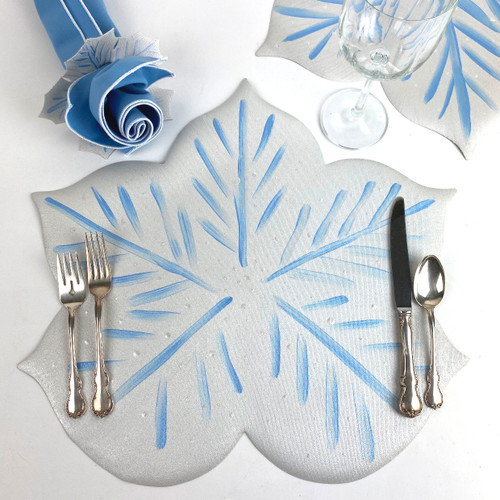 Wintery white Snowflake Placemat with blue highlights is hand-painted and comes with white/blue snowflake Napkin-Ring-to-Coaster, as shown, with light blue/white trim napkin! A beautiful winter pairing!  Layer 3 or 5 placemats when not serving to create a winter wonderland runner, while gathering the napkins and rings to create a centerpiece bouquet!