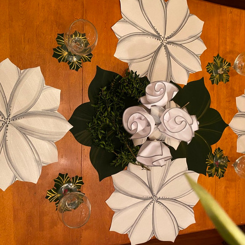 4 white floral placemats are beautifully teamed with 2 pine leaf placemats, shown as the interlocking centerpiece here; leaves can swing out to serve two more guests at the table; plus 6 napkins and rings, as shown center; plus 6 complementary hollyberry coasters, especially perfect at the holidays