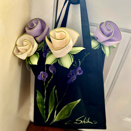 "13""H x 12""W x 8"" , Carole's Garden Tote is hand-painted with purples & greens, and comes  signed by Carole Shiber, and blooming with 4 napkins and rings ($60 retail value bouquet) that look like flowers. A very special and creative gift that presents wearable function and beauty. Or to leave out as artful home decor!"