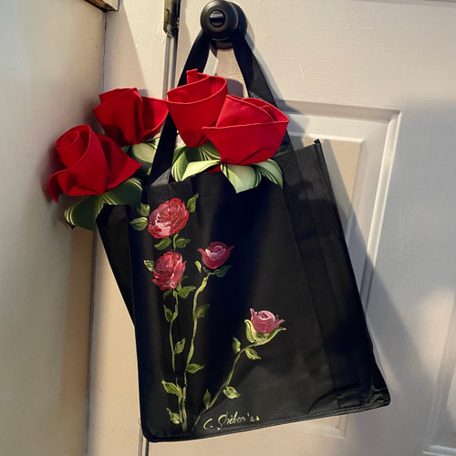 "Grand Tote (14""H x 12""W x 8"" base) is hand-painted with red/pink roses, and comes with a napkin bouquet of red napkins and green leafy hand-painted napkin rings. What an extra-ordinary gift -- and beautiful way to add a splash of color and home decor to the kitchen.  Grab it as you go out the door to run errands, while placing the long-stemmed red roses on the table for dinner later!"