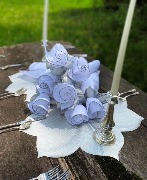 Set of 8 white/grey  napkins and rings lay atop two Interlocking white/grey Leaf Placemats to create an artful centerpiece that's as functional as it is gorgeous.