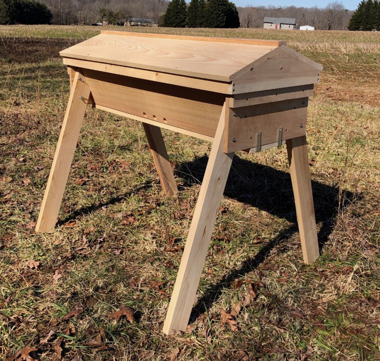 The Gold Star top bar hive - front view.  Made from sustainably harvested cypress, it comes with a light-weight, gabled roof, and sturdy removable legs.