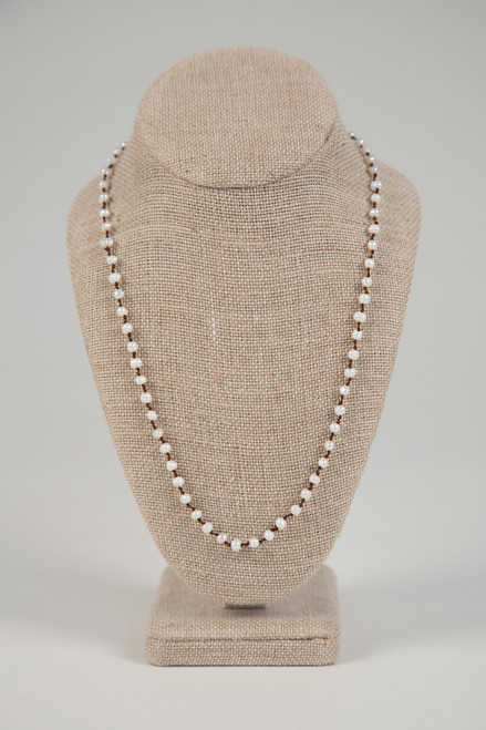 Long White Pearl Necklace on Dark Wax Cotton