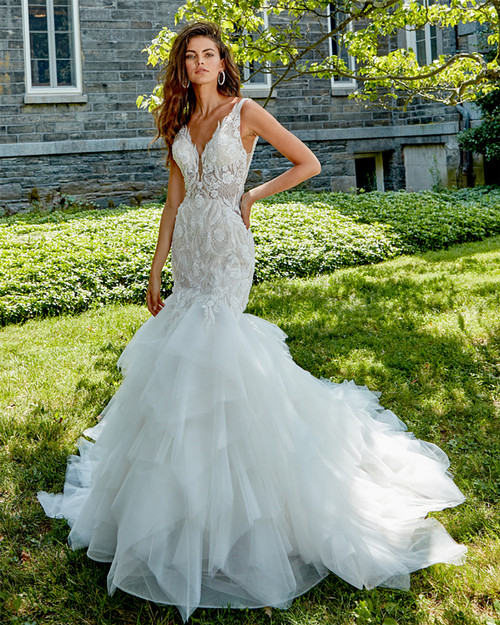 hand beaded lace v neckline, sheer bodice. Low back, Fit and Flare silhouette with whimsical skirt, chapel train with horsehair.