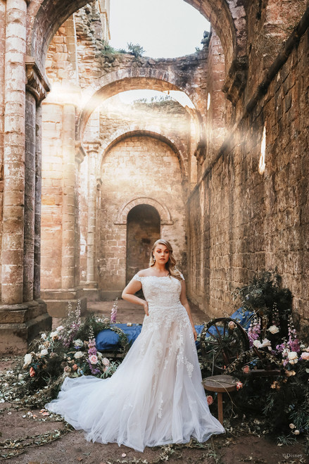 With a nod to Aurora's iconic basque waistline and graceful silhouette, this gown tapers from a sequined floral lace bodice to a subtle A-line. Delicate, exposed boning along the back of the gown and off-shoulder cap sleeves put the finishing touches on this truly elegant gown.