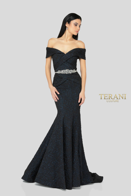 Elegant off the shoulder evening gown in tonal brocade with rose motif. The flattering bodice is features elegant draping and a crystal embellished waistline. The fitted skirt opens up to a beautifully structured mermaid bottom.