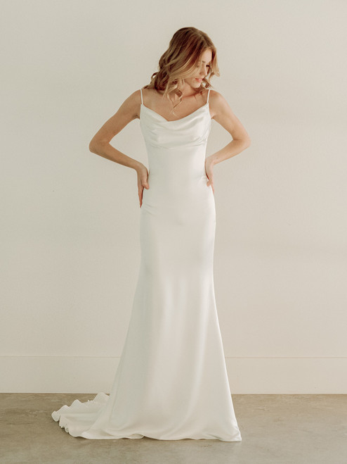This gorgeous clean gown features luxurious satin back crepe with a delicate bodice-draping. It is finished with a beautiful cowl back neckline.