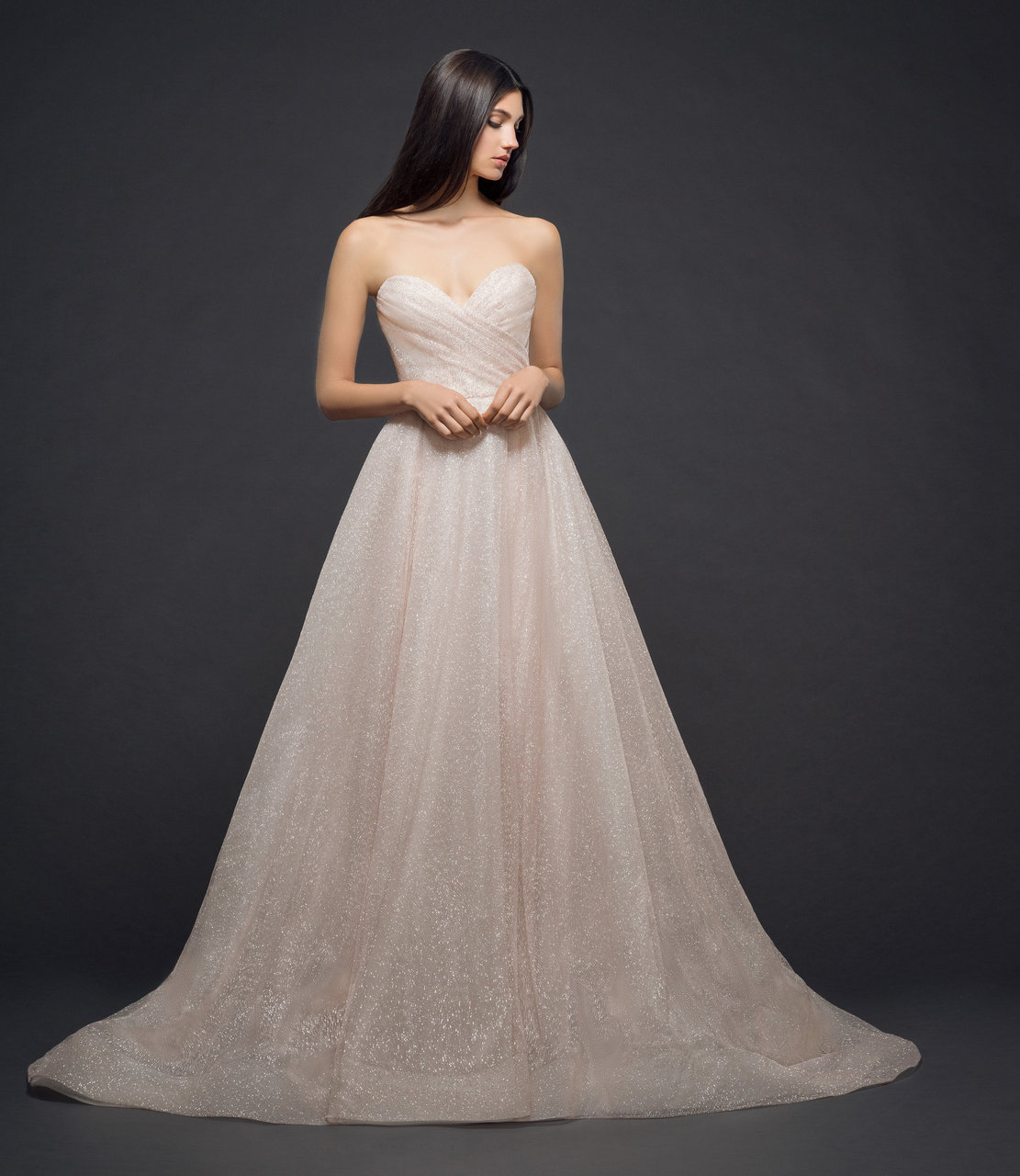 Blush shimmer tulle ball gown, strapless sweetheart neckline, draped bodice and natural waist, box pleated skirt with side pockets, chapel train.