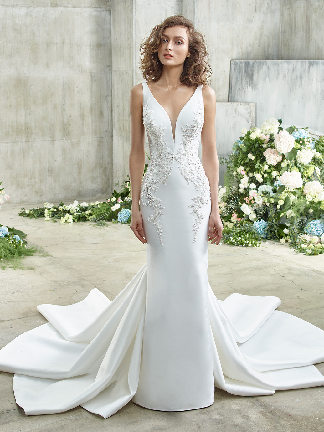 Modern elegance takes on a whole new meaning in Eunice, featuring exquisite, sparkling beaded embroidered lace over sleek, supportive, and ultra-chic mimosa fabric. A plunging V-neckline is subtly modest with an illusion tulle inset piece, while the low, illusion lace V-back is all glitz and glam as it trickles down into a gorgeously dramatic mermaid skirt.