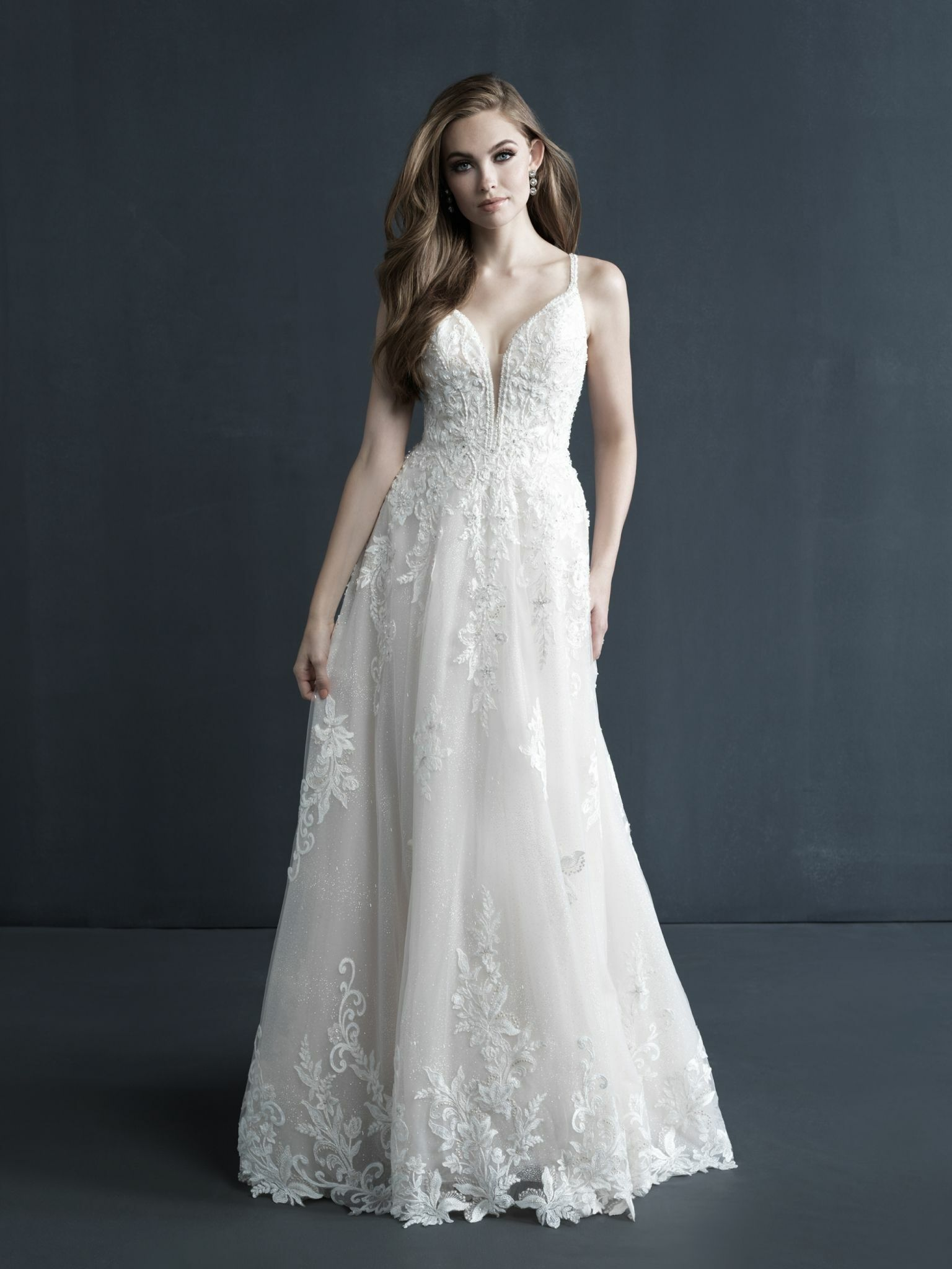 Twinkling beadwork sparkles across the lace appliques of this A-line gown.