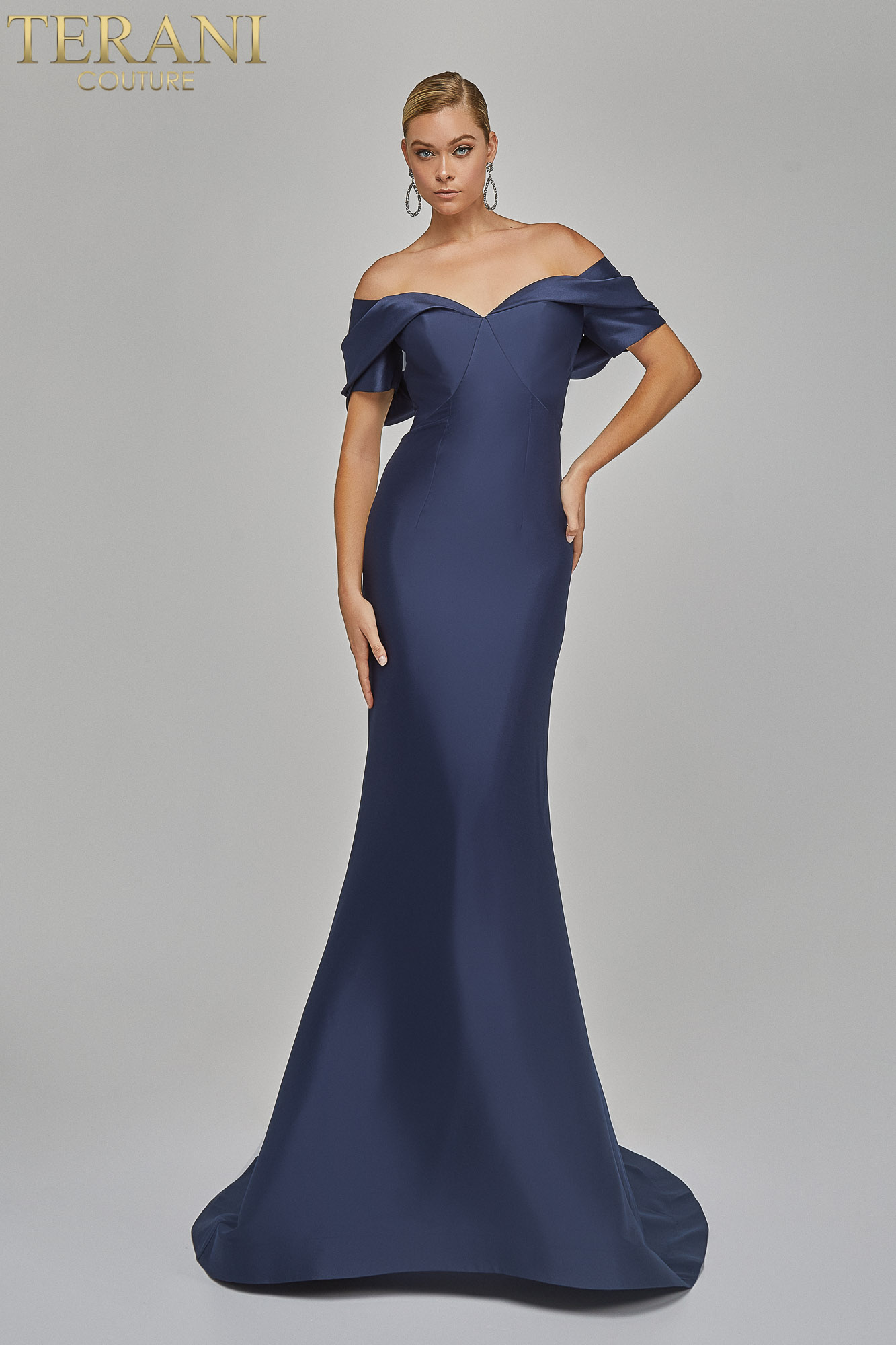 Eye catching off shoulder collar drapes over a plain stretch evening Mikado gown with tail.