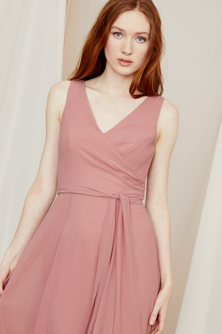 Perfectly draped and ruched to create the illusion of a wrap silhouette, this V-neck bridesmaid dress in smooth chiffon ties at the waist and zips high at the back.