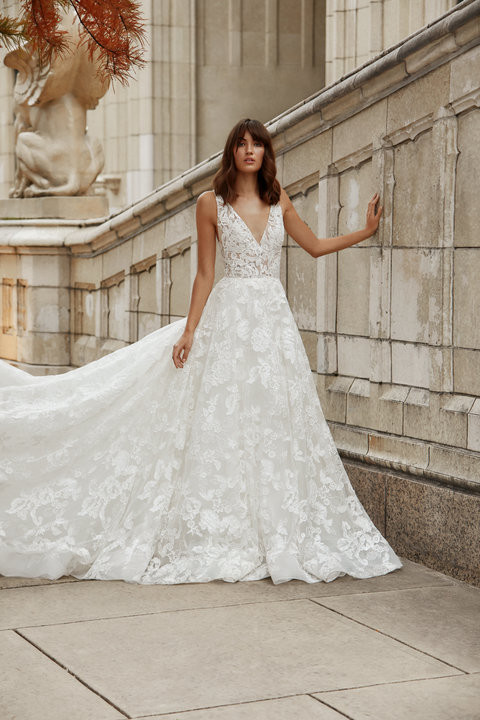 Ivory Alencon lace A-line gown, V neckline front and back, shear lace appliqued bodice, circular skirt with horsehair at hem, chapel train.