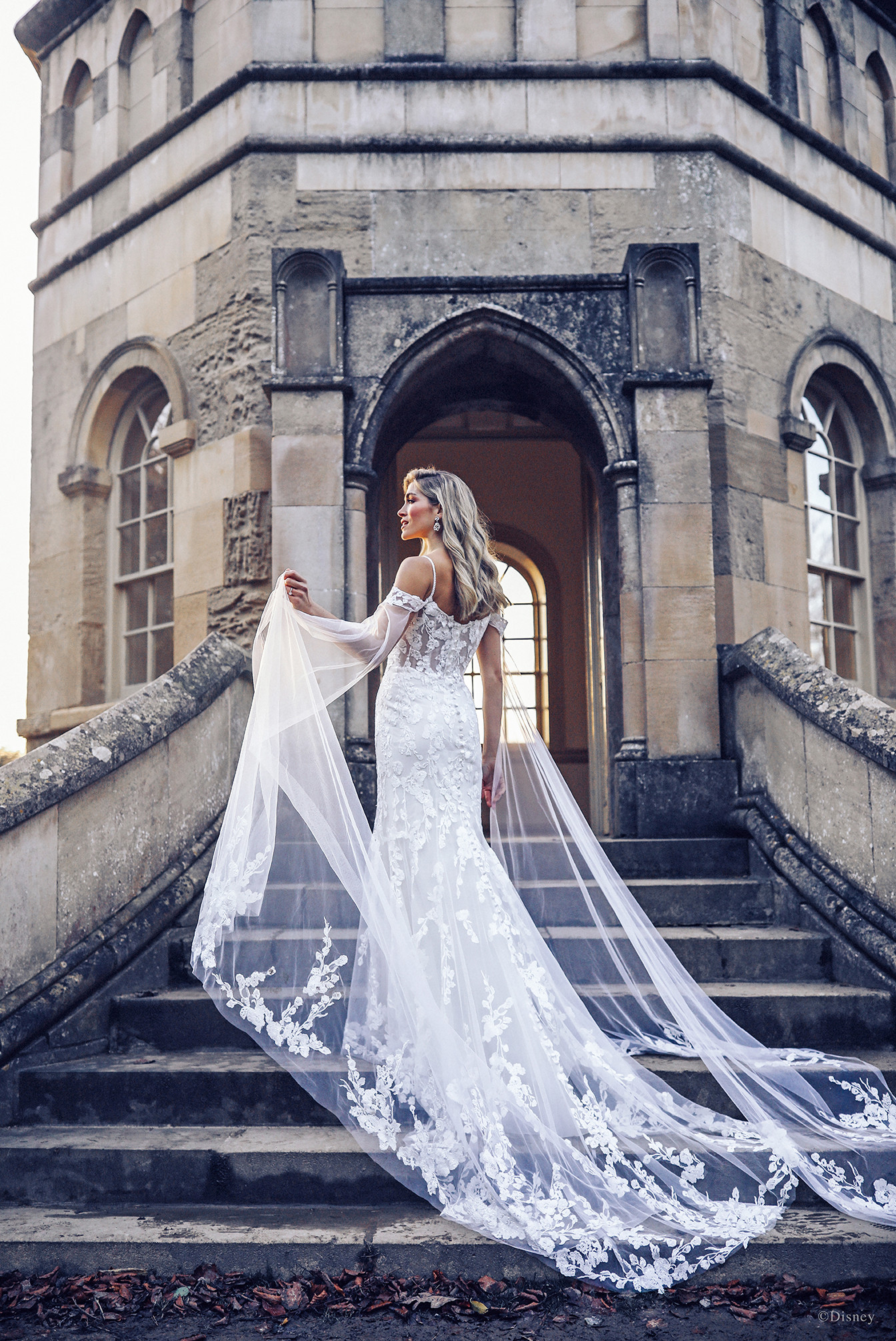 Dual illusion capes cascade down the silhouette of the Rapunzel-inspired gown, echoing the Princess's floor-skimming locks. The sheath gown is sprinkled with tiny blooms and finished with cold shoulder lace cap sleeves.