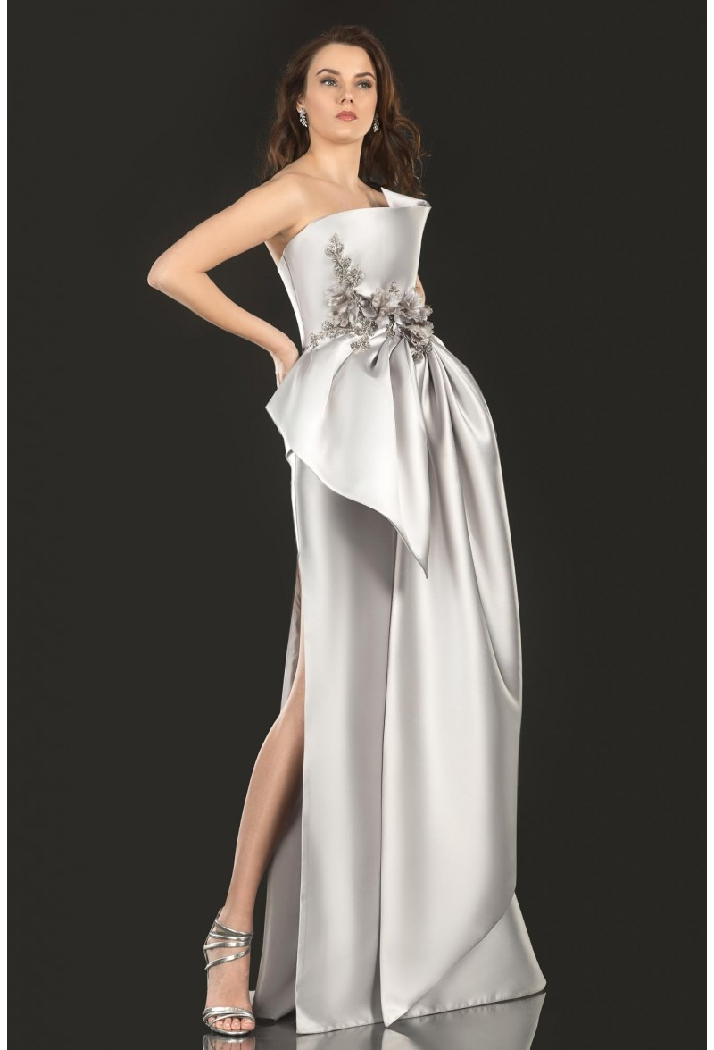 Three-dimensional sculptured bodice has a cascading flower and beads with oversized draped bow skirt.