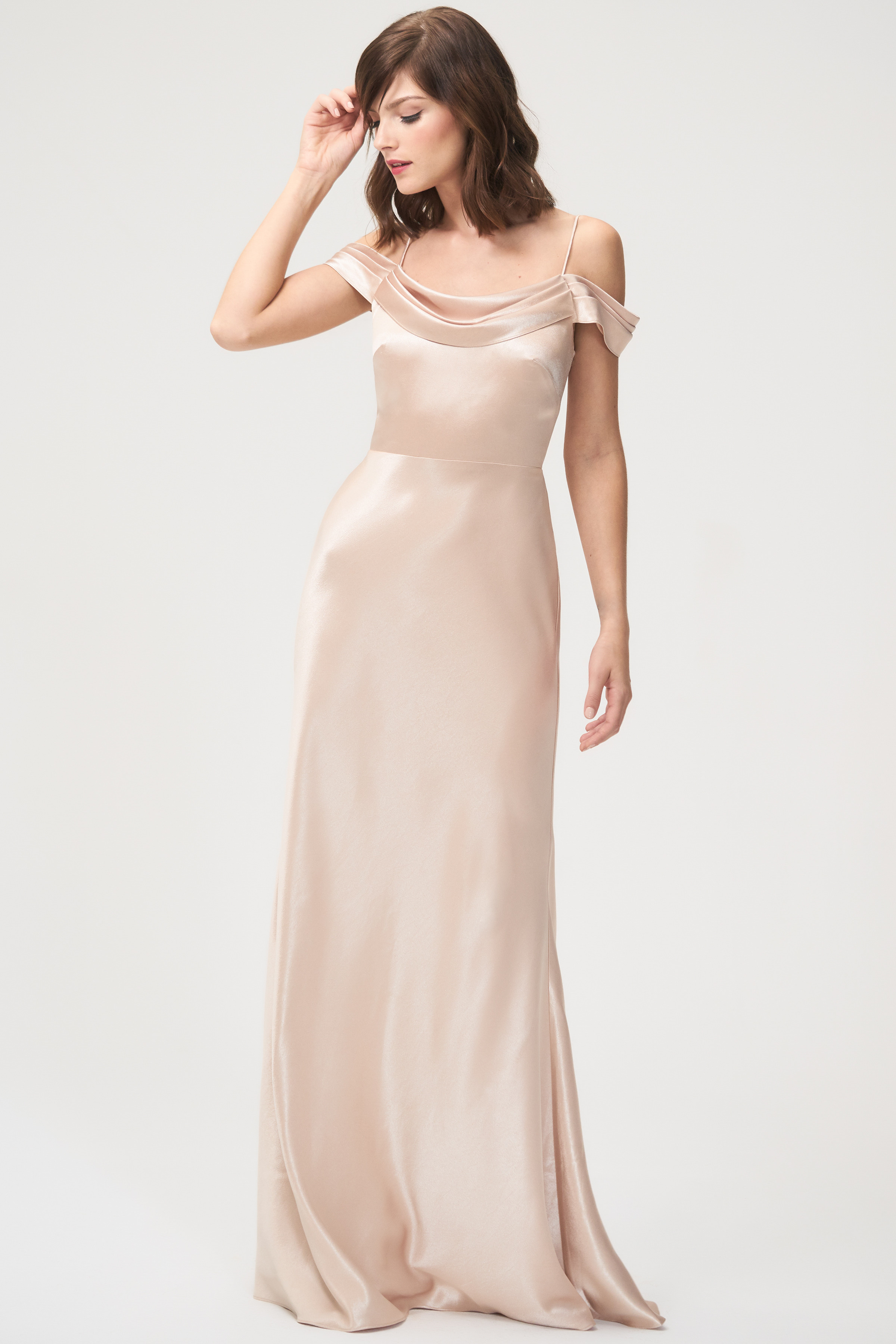 The Serena dress has a pleated cowl neck for a dramatically stunning effect with pleated and draped off-the-shoulder straps adding visual interest. The floor length bias-cut skirt creates a romantic, modern look. The dress is bodice lined with a center back zipper.