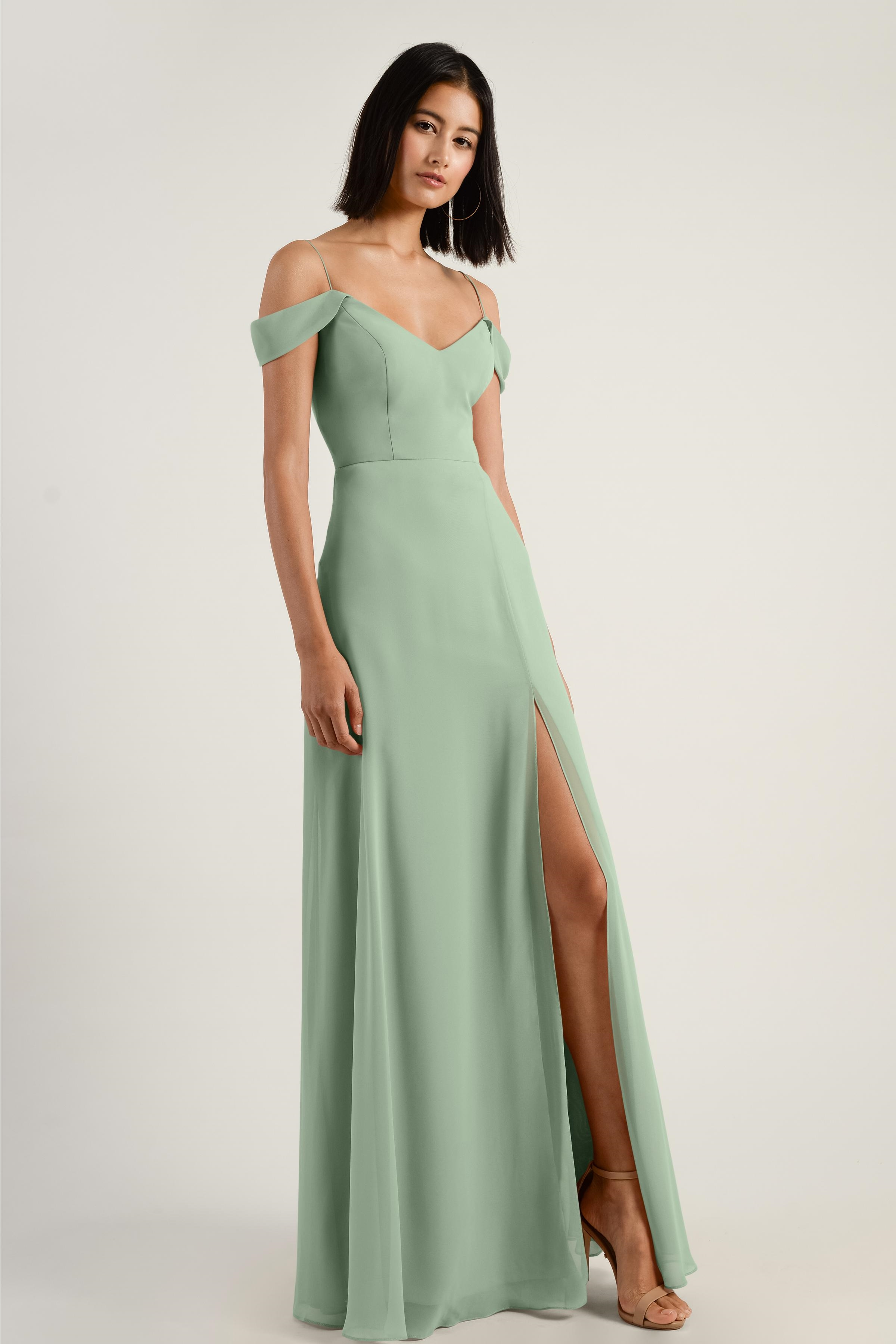 The Priya dress has a flattering soft A line silhouette with a spaghetti strap V neckline in our flowy Luxe Chiffon. An modern off the shoulder folded sleeve slopes into a soft V in the front and back of the bodice. The defined waist gives way to a long skirt with a flirty above the knee princess seam slit. This bridesmaid dress is fully lined with an invisible center back zipper.