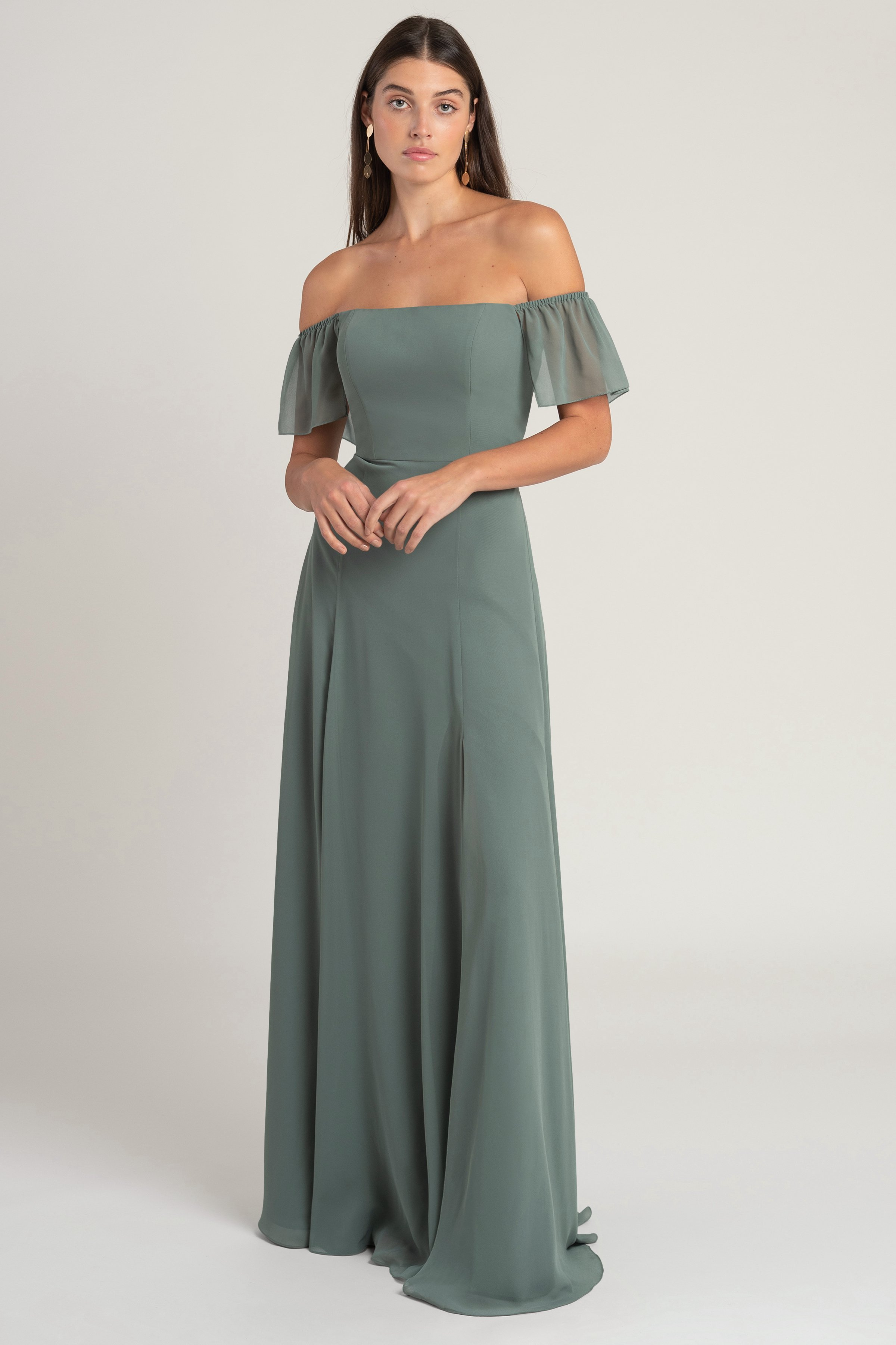 The Elsie is an off the shoulder flutter sleeve chiffon bridesmaid dress that takes a modern approach to romance. The skirt has beautiful movement while remaining slim through the hips for an incredibly flattering silhouette. The addition of a side slit adds one more flirty touch.