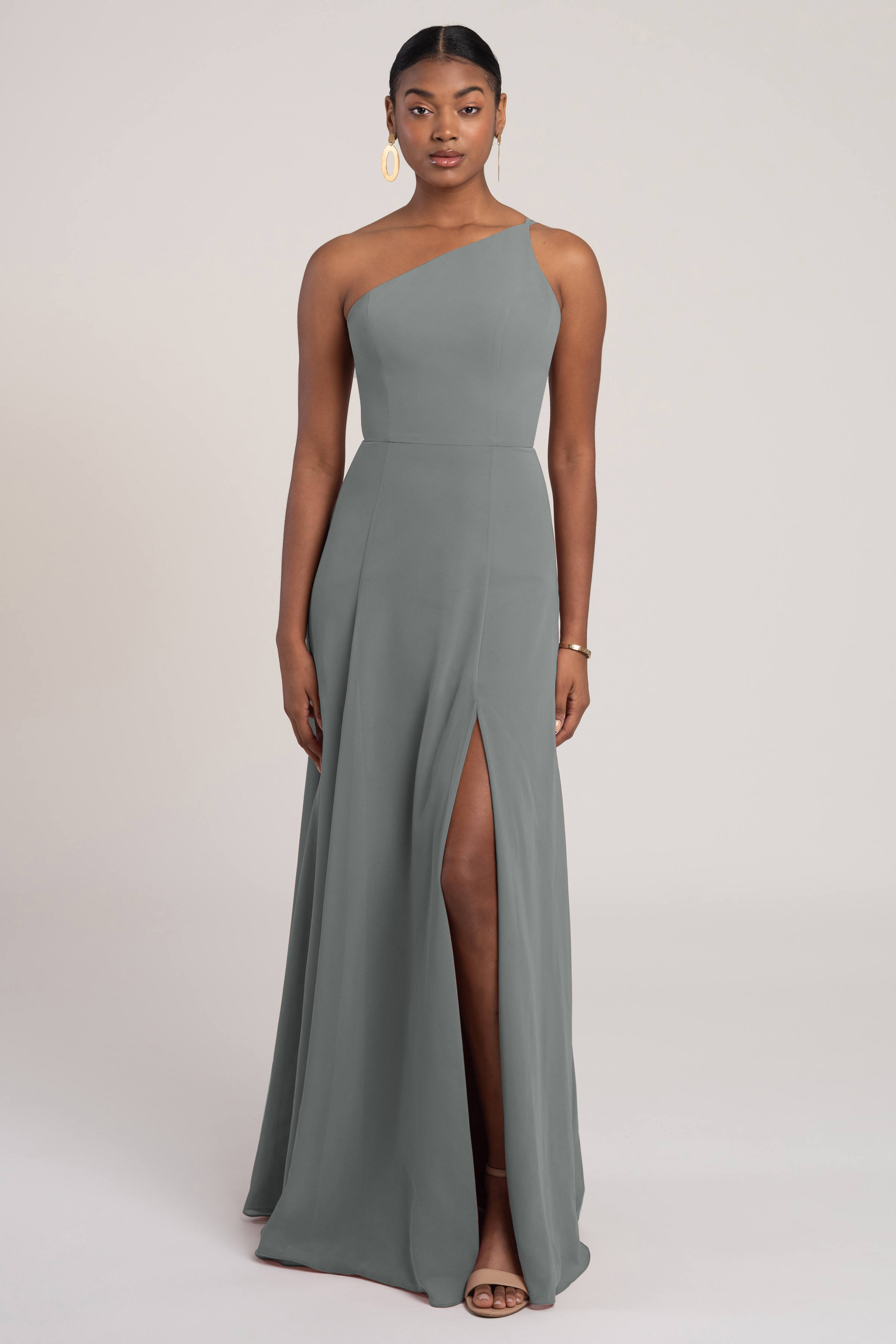 The Kora one shoulder chiffon bridesmaid dress features clean styling and subtle details that make her a beautifully elegant addition to any bridal party. The skirt is cut slim through the hips for a flattering fit and flare silhouette. The delicate asymmetrical straps frame the back and show off your shoulders for a stunning modern look from front to back.