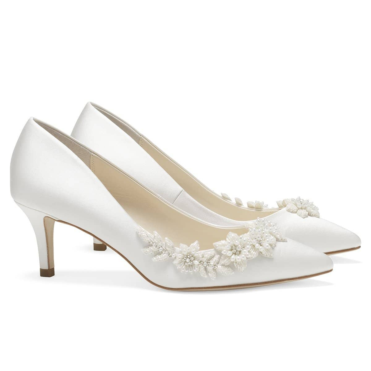 The perfect ivory or light blue heels wedding guests will admire, Iris Blue. These blue kitten heel wedding shoes embody tradition re-imagined and re-defined. Teardrop luminous pearls and ivory beads are embellished in the shape of flowers and vines sweeping the side of these blue kitten heels wedding shoes. The 3D ivory blooms and vines provide textural contrast to the soft blue silk. These blue low heels wedding occasion pieces provide comfort, tradition, and style.