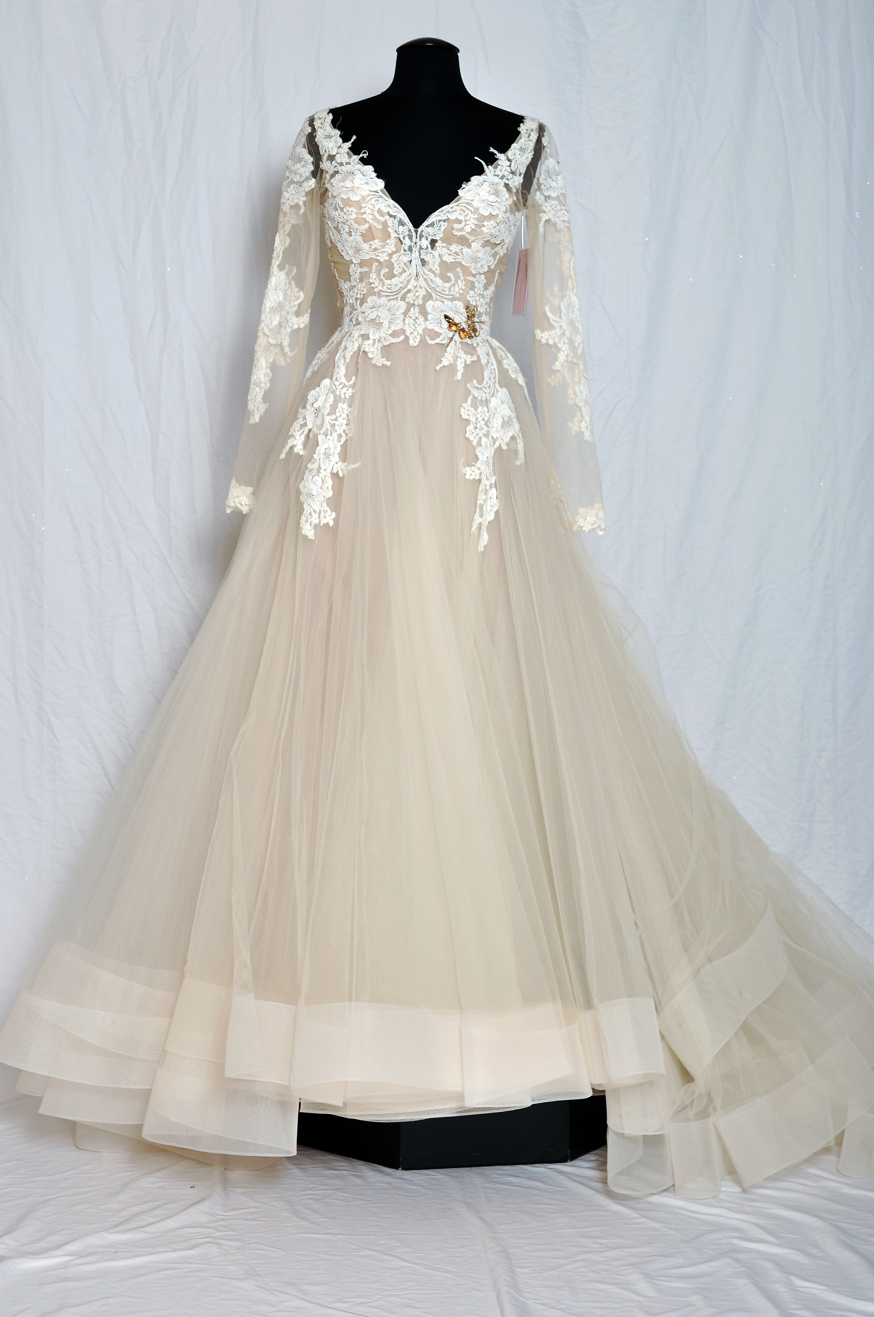 Ivory/champagne alencon lace appliqud tulle bridal ball gown, sculpted V-neckline with curved back, sheer long fitted sleeve, crystal butterfly broach at natural waist, circular skirt with horsehair at hemline, chapel train.