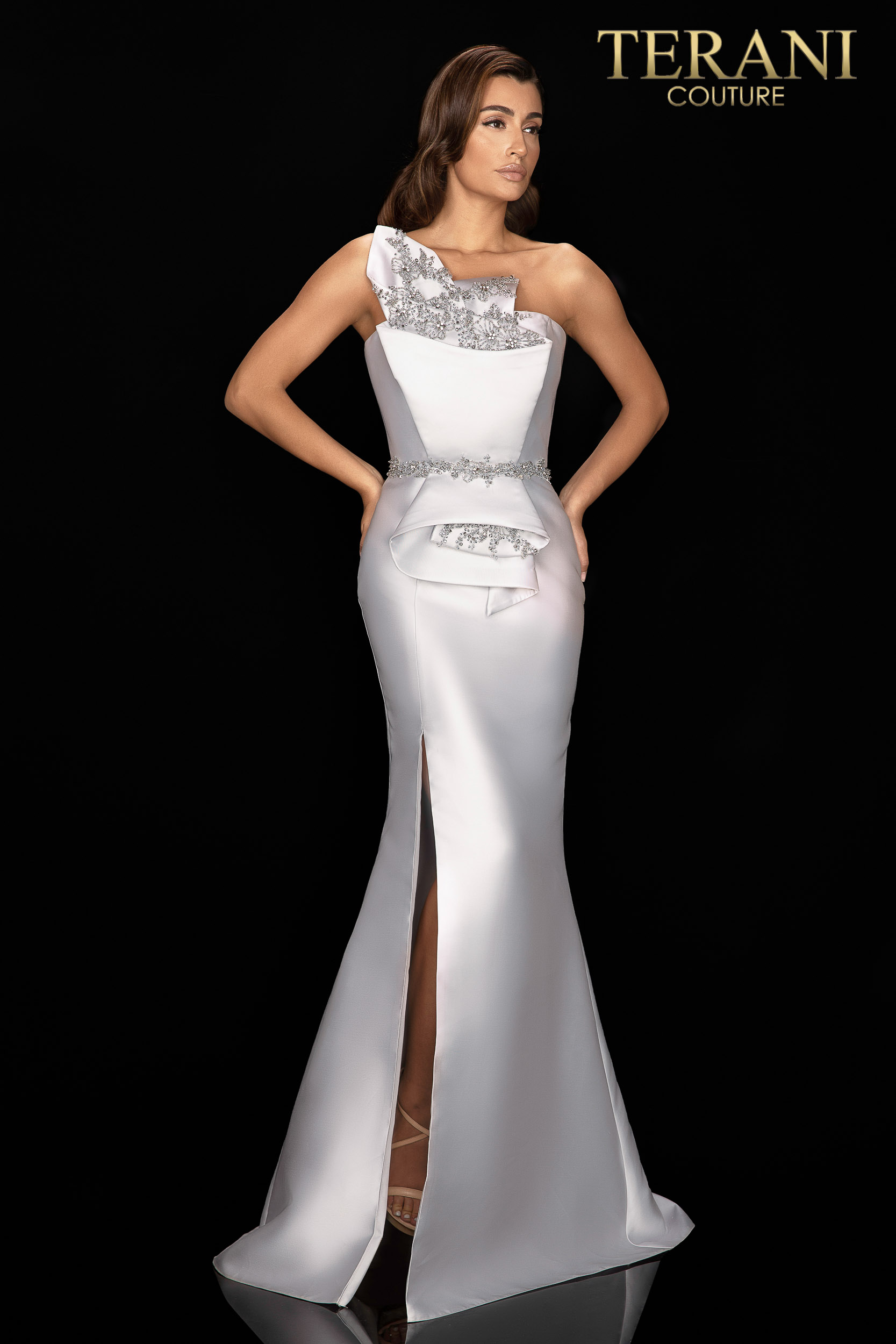Architectural wrapped torso gown detailed with stones. This slim fit gown has one shoulder and side slit