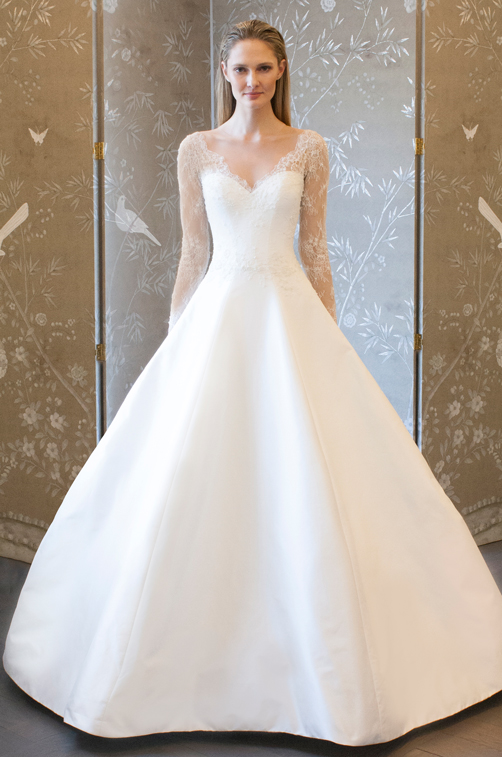 Natural white a-line ballgown made of silk shantung taffeta, features an illusion long sleeve V-neck bodice made of beaded chantilly lace.