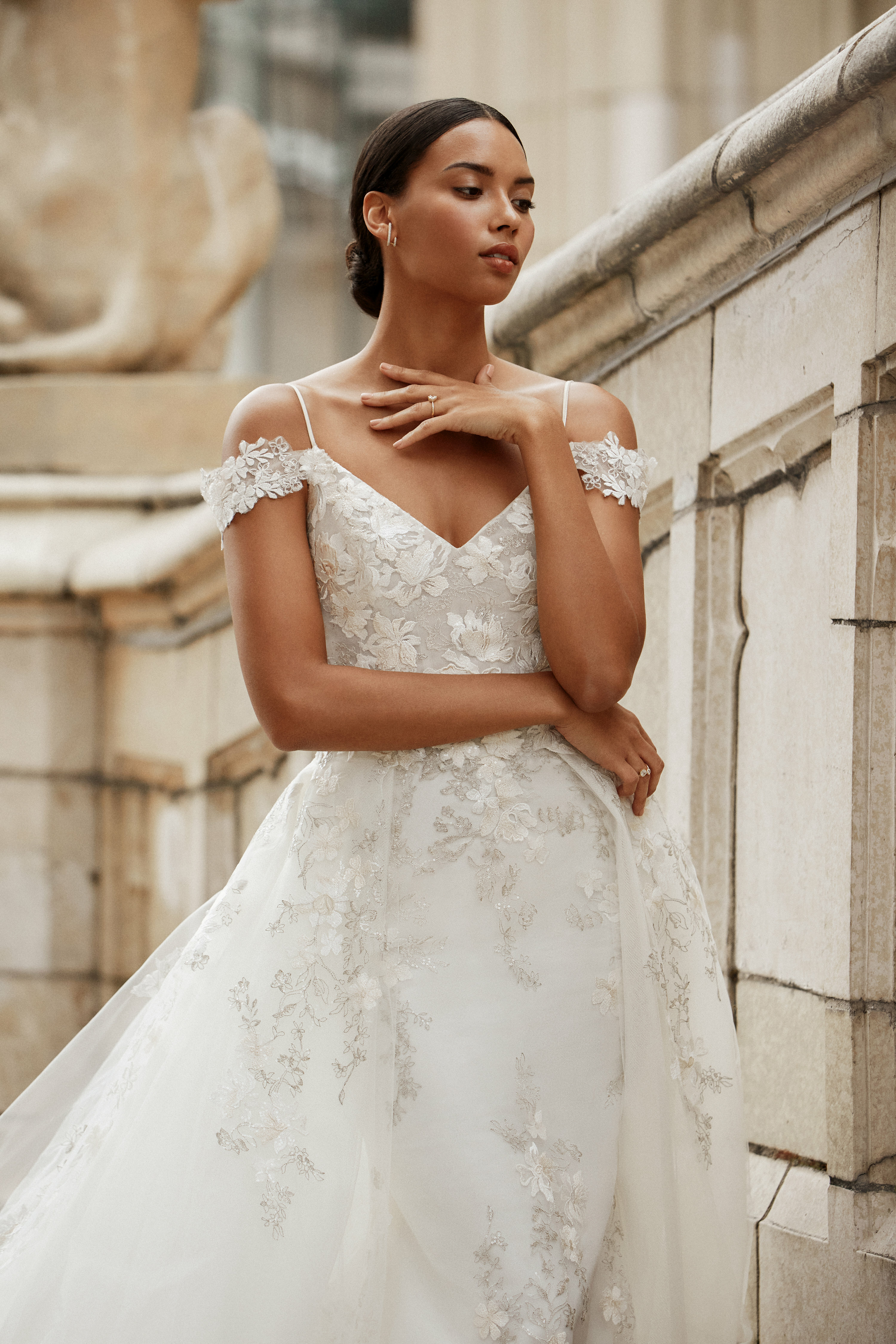 Ivory floral embroidered two-piece gown, strapless sweetheart neckline, off the shoulder sheer cap sleeve, corset bodice, natural waist, trumpet skirt with sweep train. Detachable tulle skirt with cascading floral appliques starting at waist, horsehair trim at hemline, chapel train.