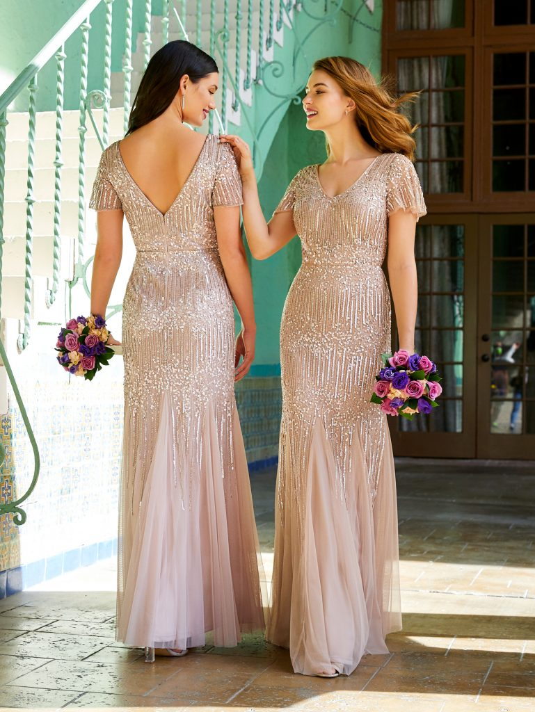 Artisanal floral beading can best describe this slim mesh gown with short sleeves, v front and back bodice and soft godets in the skirt. A perfect look for bridesmaids but watch for moms to have their eye on this gown too.
