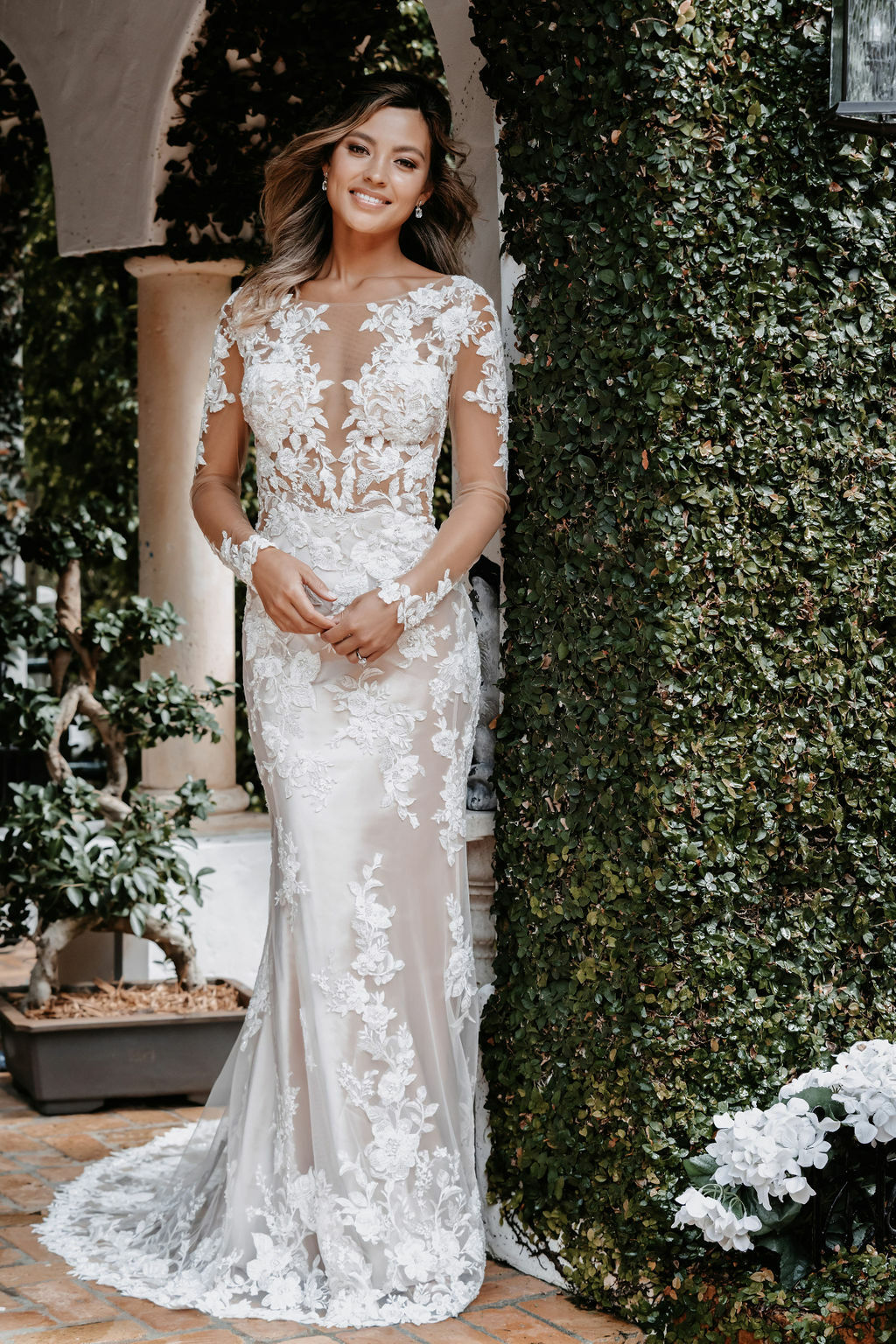 A truly unforgettable gown, this illusion sleeved sheath features the most delicate lace throughout the overskirt and bodice.
