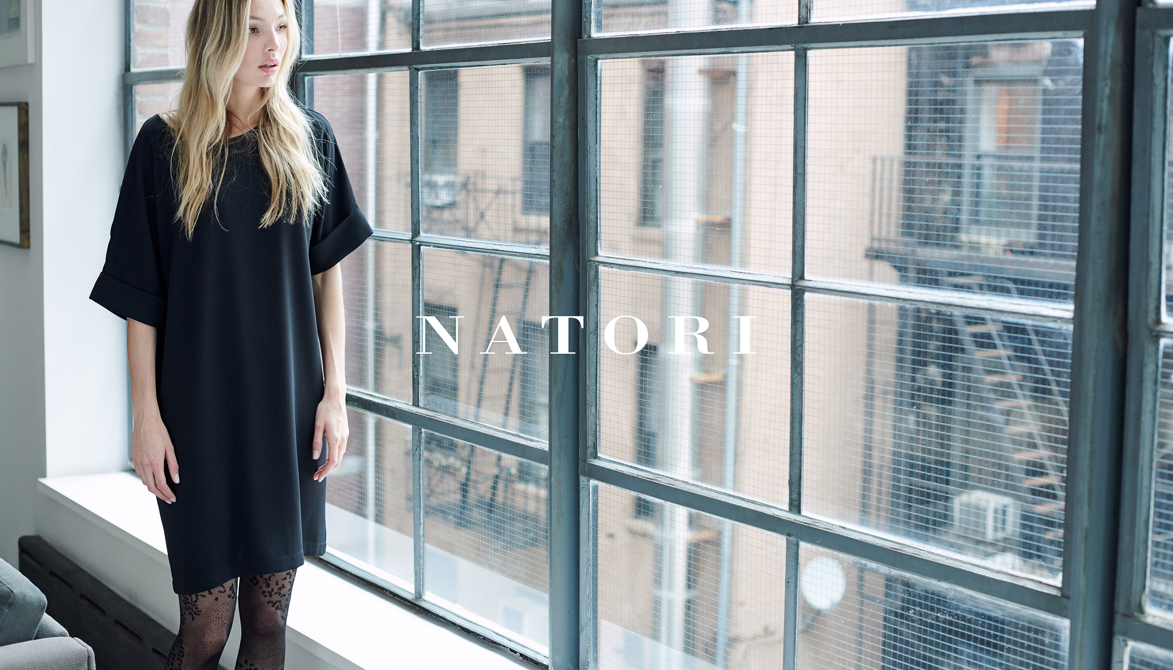 Natori model looking out the window wearing black dress