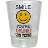 Glass Las Vegas shotglass with a design on the front which has a yellow smiling face. Says Smile You're Drunk Las Vegas.