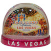 Clear plastic snowdome with a pink base. Inside has a Vegas welcome sign design with dice on the graphics. White snow swirls around on the inside.