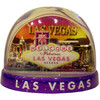 Clear plastic snowdome with a purple base shown. Inside has a Vegas welcome sign design with a beautiful sunset on the graphics. White snow swirls around on the inside.