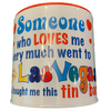 White tin bank in cylinder shape with colorful words Someone who loves me very much went to Las Vegas and brought me this tin bank.