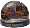 Clear plastic snowdome with a dark blue base. Inside has a Vegas welcome sign design with casinos on the graphics. White snow swirls around on the inside.