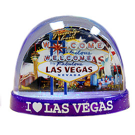 Clear plastic snowdome with a Purple base. Inside has a Vegas welcome sign design with the US Flag on the graphics. White snow swirls around on the inside.