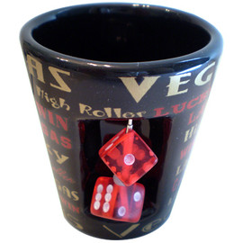 "Ceramic Black Las Vegas  shotglass which has spinning mini dice on the front and ""Las Vegas"" in gold and red lettering in different fonts all over it."