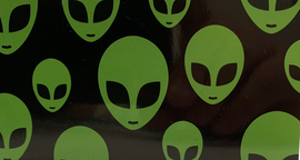 "Beach Towel with black background and green ""Alien Faces"" print all over it."