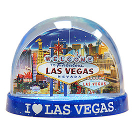 Clear plastic snowdome with a blue base. Inside has a Vegas welcome sign design with Casinos on the graphics. White snow swirls around on the inside.