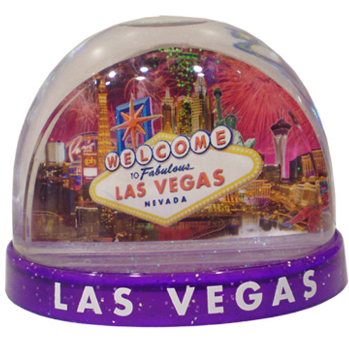 Clear plastic snowdome with a Purple base. Inside has a Vegas welcome sign design with fireworks on the graphics. White snow swirls around on the inside.