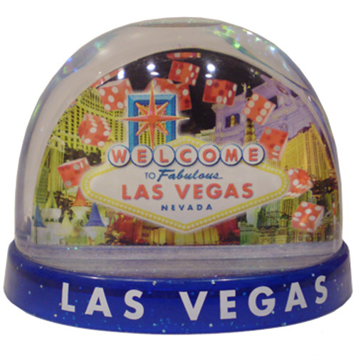Clear plastic snowdome with a blue base. Inside has a Vegas welcome sign design with dice on the graphics. White snow swirls around on the inside.