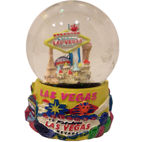 Acrylic base and a Glass Snowglobe. Base is yellow with colorful icons. Inside the snowglobe has glitter snow and colorful 3D versions of the Las Vegas Casinos and Welcome Sign that you know and love.