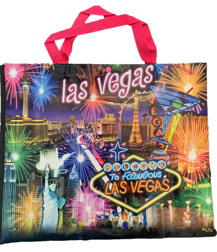 Pink handled, black background tote bag shows a Las Vegas at the top over the Las Vegas Casinos in bright colors with fireworks bursting overhead.