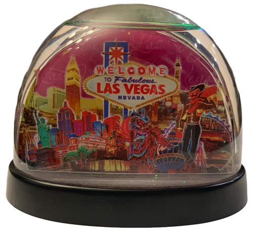Clear plastic snowdome with a pink base. Inside has a Vegas welcome sign with a Pink Skies design on the graphics. White snow swirls around on the inside.